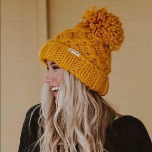 Loose knit winter hat with oversized pom